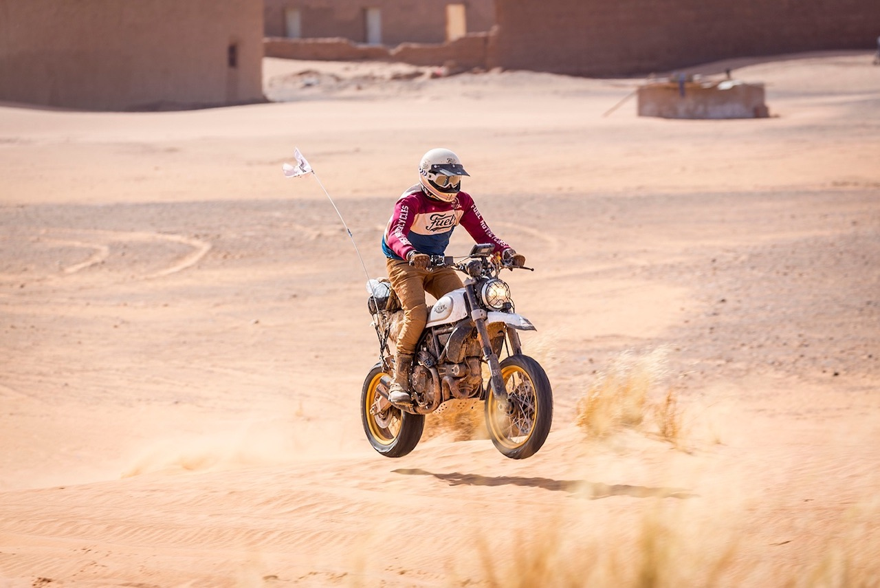 Man riding a motorcycle across the desert wearing FUEL Sergeant Motorcycle Trousers Sahara