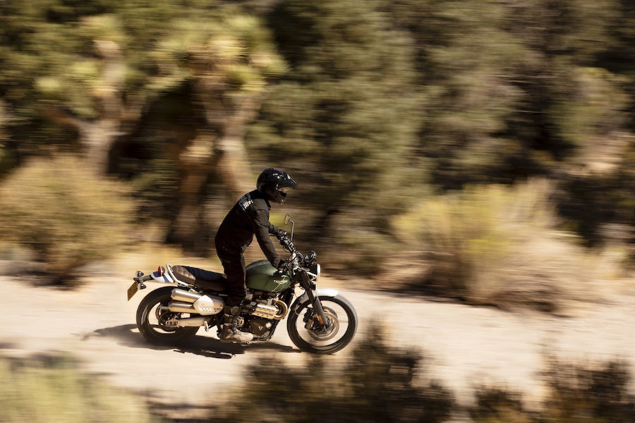 Green Triumph Scrambler 1200 XE with rider on trails