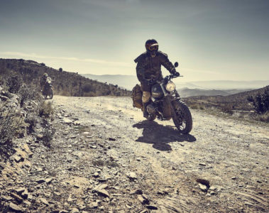 Rider on a BMW Scrambler wearing Old Western style overcoat