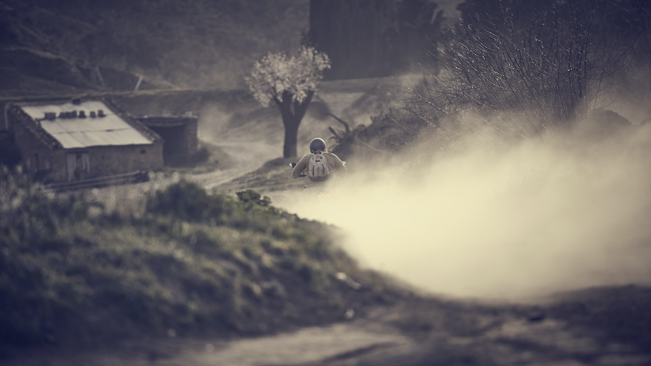 Rear view of rider on a motorcycle riding down a dusty hill
