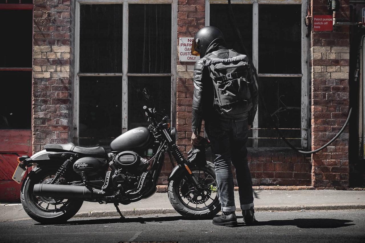 Rider wearing helmet viewing Hyosung Aquila Grand Voyage 125S